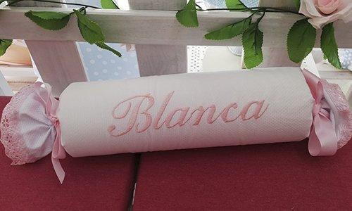Cojín antivuelco en color blanco con nombre bordado en rosa